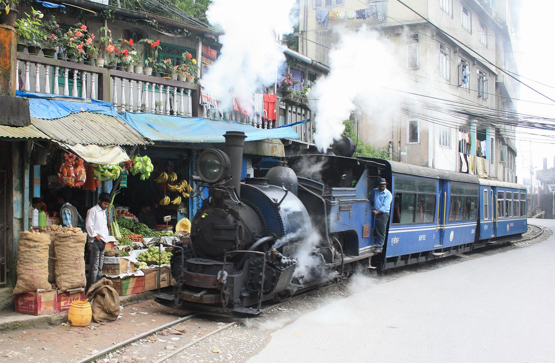 """Als """"Dampfstra-ßenbahn"""" verkehrt der Zug in Darjeeling kurz vor Erreichen der Endstation: Der Obst- und Gemüsehändler lässt sich dabei nicht stören. (Foto: Arne Hückelheim/Wikipedia)"""